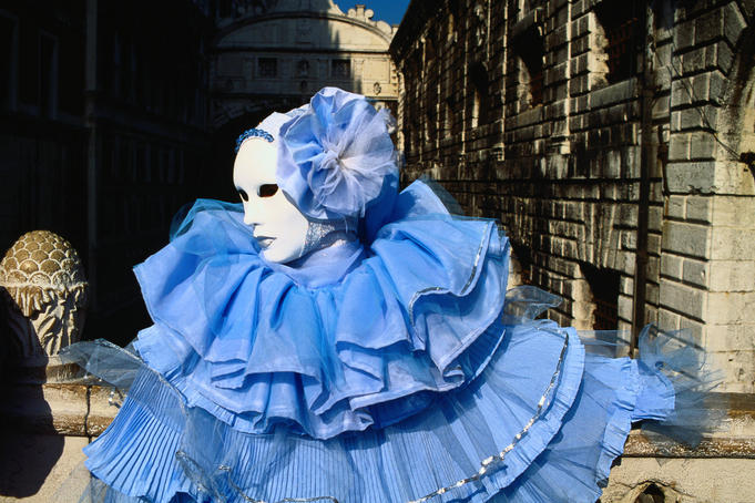 Person wearing a plain white mask and delicate blue costume during the Venice Carnival ( Carnevale ); a ten day street party leading up to Ash Wednesday, and a time to dress elaborately, and don spectacular masks - Venice, The Veneto
