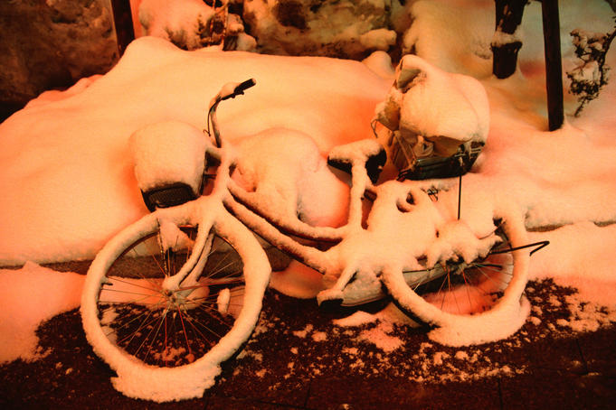 An abandoned bicycle under snow, painted with a red glow from neon in the entertainment quarter in Susukino.