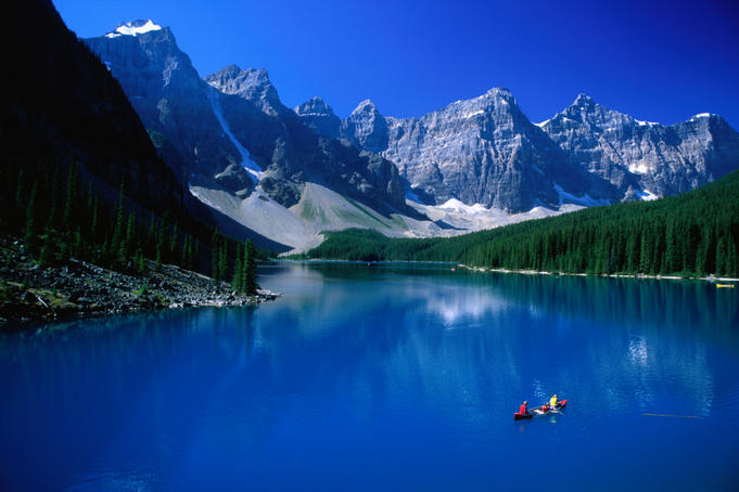 People paddling their canoe on the impossibly blue waters of Moraine Lake, surrounded by the Rocky Mountains in the Banff National Park.