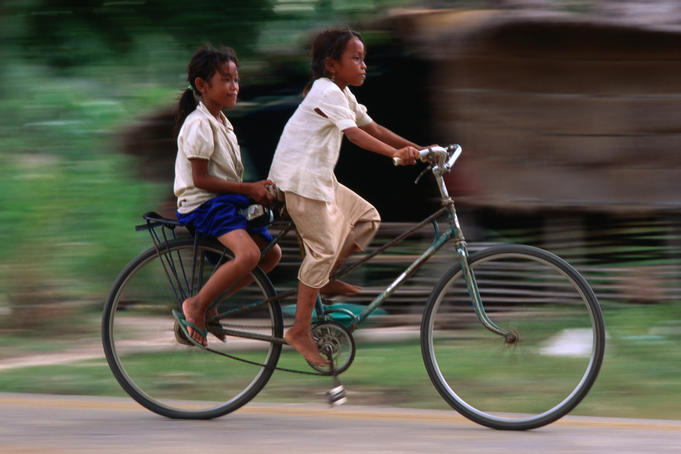 Girls riding bicycle in Bavel village.