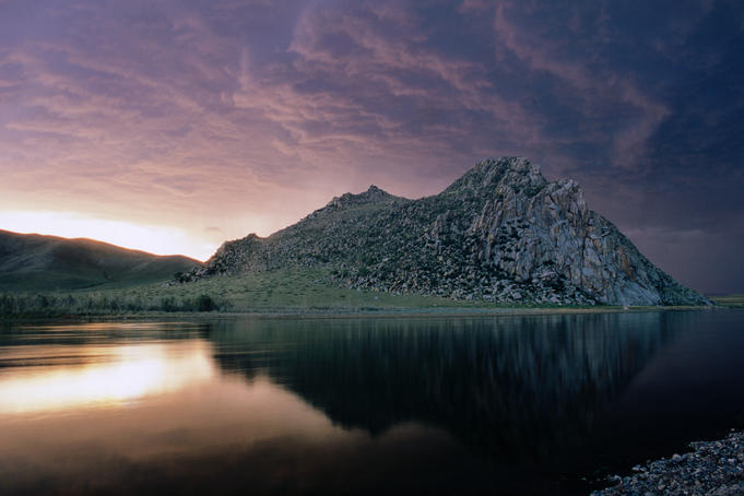 Mountain by a lake at sunset.