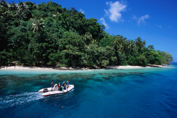 Divers in a small boat travel past an island beach.