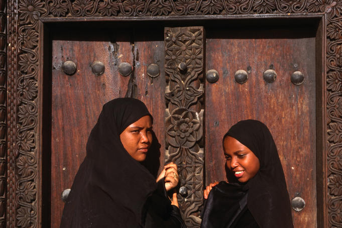 Young Islamic girls in traditional bui-bui stand in front of a typical Zanzibar doorway in Lamu.