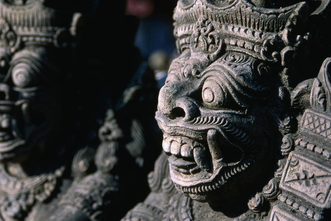 The fierce, defensive face of a Raksas (nocturnal demon) carved in stone in Batubulan.