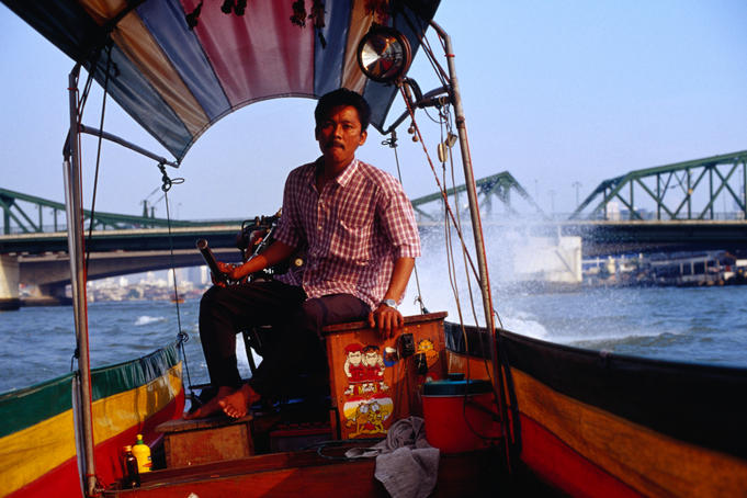 Driver on long tail boat on the Chao Phraya (River).