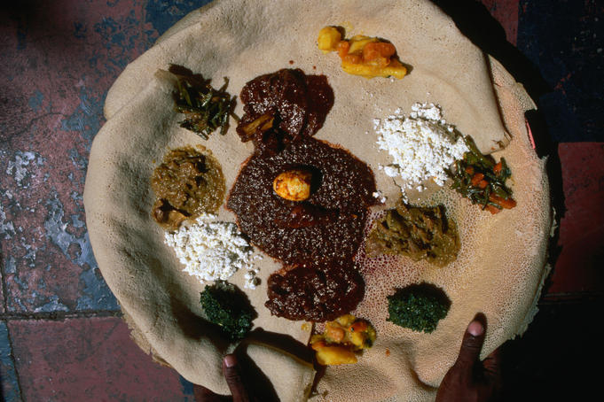 Various traditional Ethiopian dishes served on injera in an Ethiopian Restaurant