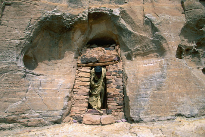 A priest exits through the stone doorway in a rock cliff face; the main entrance to the well-concealed church of Abuna Yemata, near Hawsien