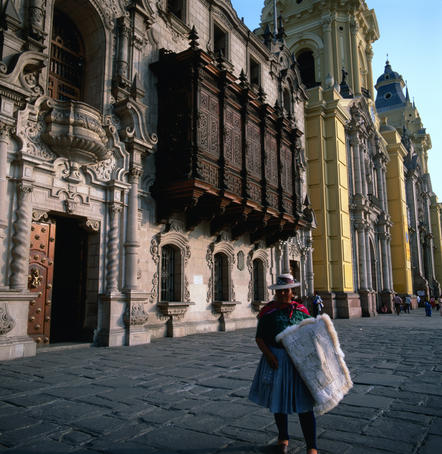 A Quecha lady standing in front of the Archbishop's Palace and Colonial Cathedral of Lima.