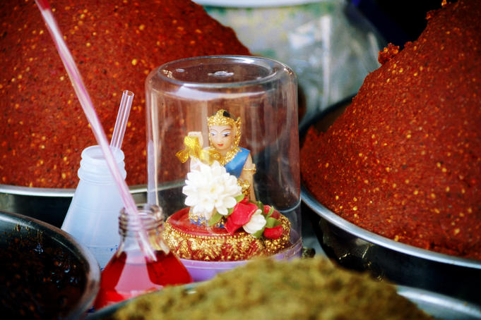 Small figurine amongst red and green curry paste.