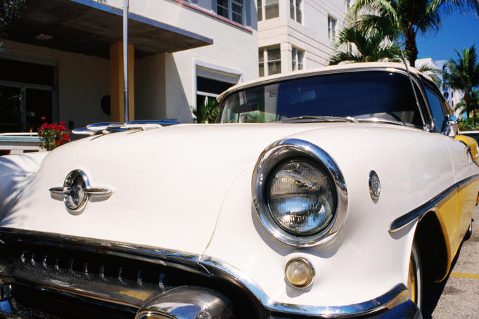 A 1957 Oldsmobile yellow convertible in front of the Avalon Hotel.