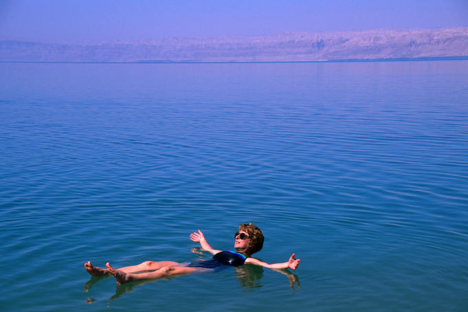 Floating on the Dead Sea in Jordan. Extremely deep (averaging about 1000ft) the sea is the lowest body of water in the world.