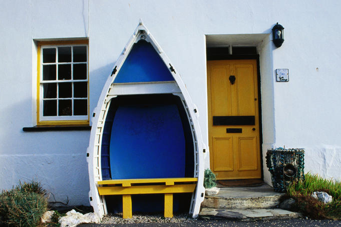 White-washed cottage with outdoor seat in old boat.