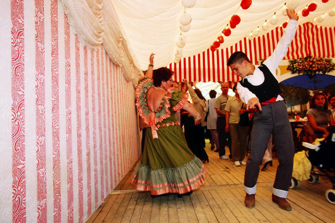 People in traditional dress dancing Sevillana inside caseta (marquee) during Feria de Abril fiesta.