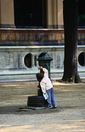 Young girl drinking from public water fountain - Milano, Lombardia