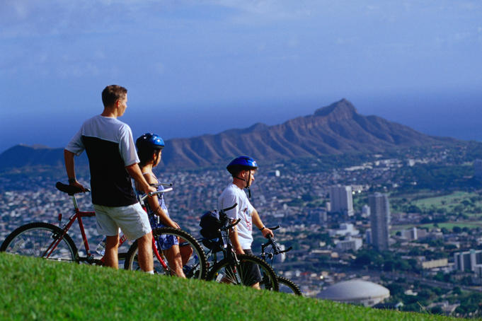 Cyclists taking in the view of Honolulu from Mt Tantalus, Pu'u Ulaka'a State Wayside Park.