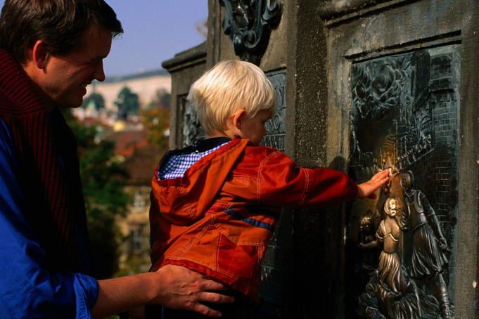 A young boy touching the St John of Nepomuk plaque (patron saint of the Czechs) on St Charles Bridge for good luck.