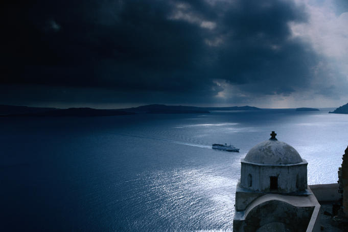 Looking down over the small Greek Orthodox chapel to an approaching ferry in the bay of Santorini.