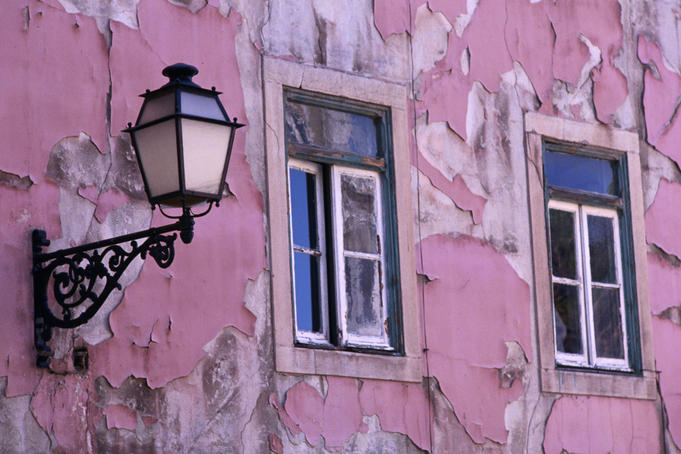 Pink paint peeling on exterior of old building in Alfama.