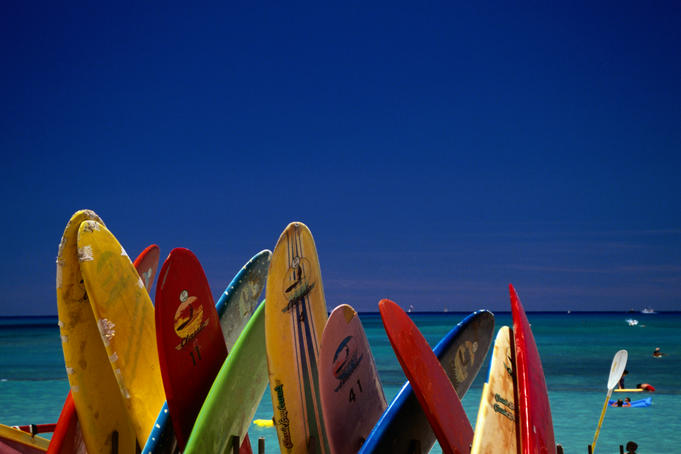 Formation of surfboards on beach with ocean in background.