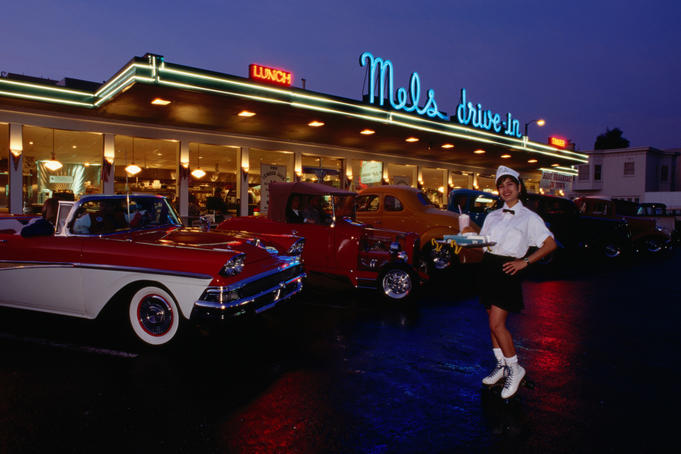 Roller skating waitress outside 1950's diner with classic cars lined up out front.