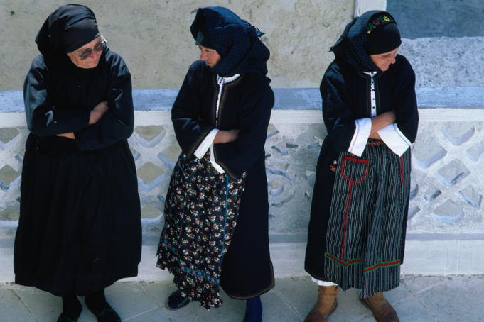 Three women in traditional dress at the Festival of Assumption of Mary.
