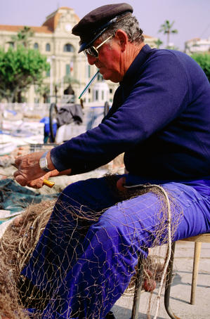 Fisherman mending net at harbour.