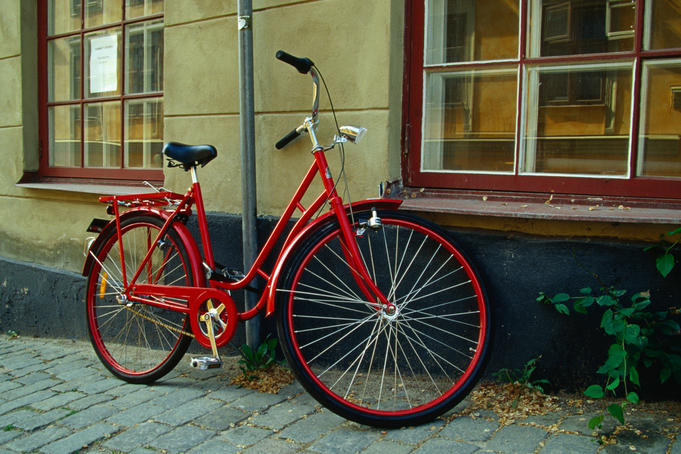 Red bicycle against old house.