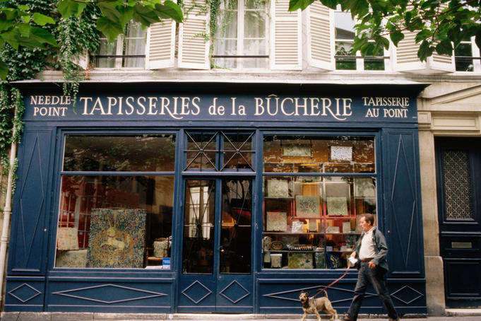Man walking dog outside Tapisseries de la Boucherie needlework shop.