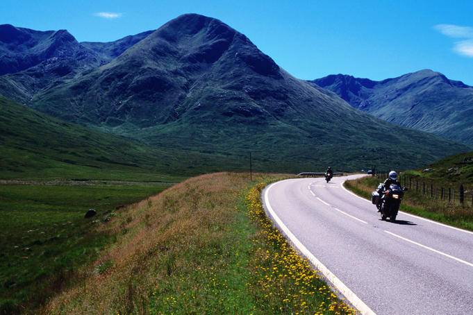 Motorcycling with mountains in background.