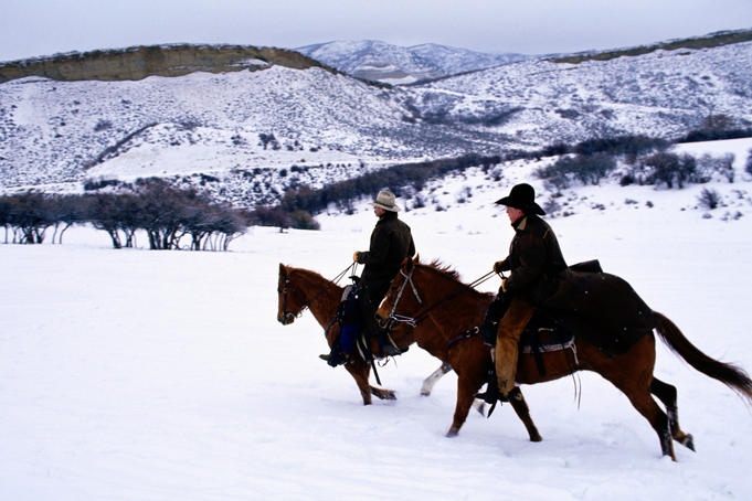 Cowboys galloping through snow.