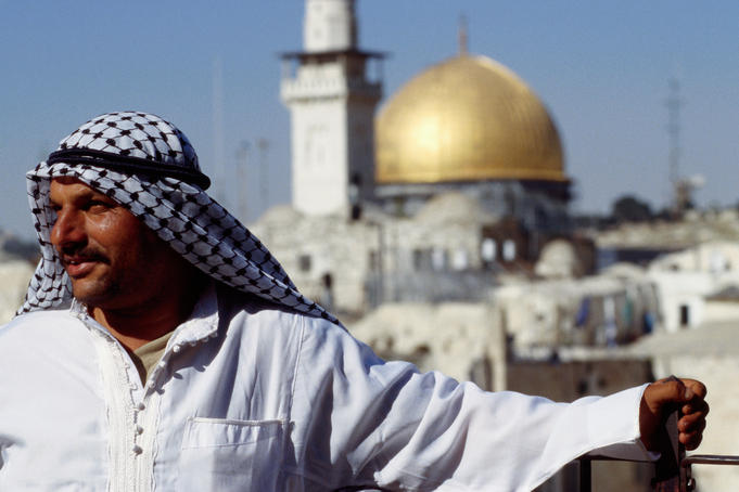 Man standing in front of the Dome of the Rock.