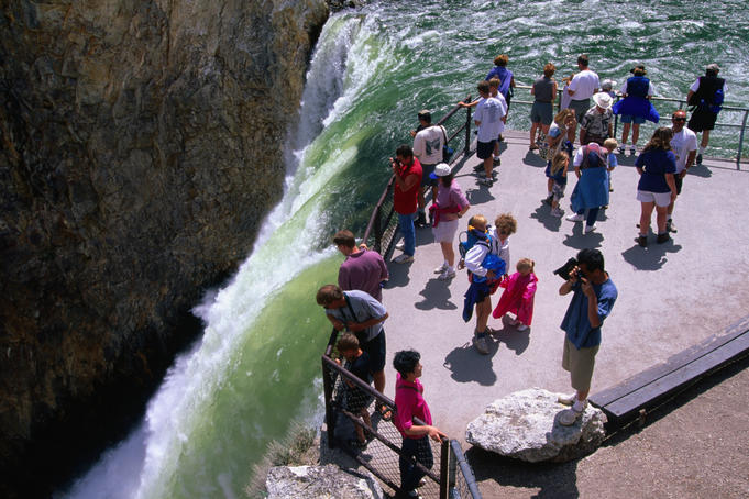 Tourists on the Lower Falls lip, Yellowstone Falls in Yellowstone National Park.