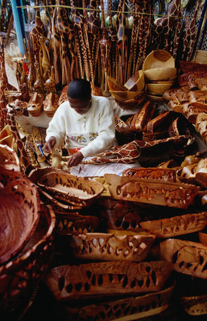 Craft for sale: A woman producing wooden souvenirs at Bruma Market World