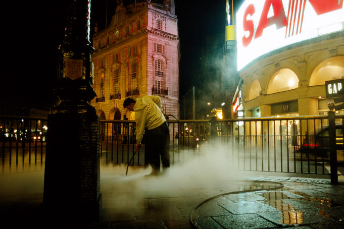 Street cleaner at Piccadily Circus at night.