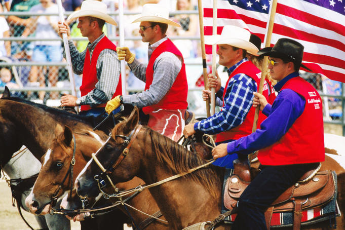 Cowboys holding an American flag on horseback in rodeo arena during rodeo competition at Mashantucket Pequot Tribal Nation hosted Schemitzun Powwow.