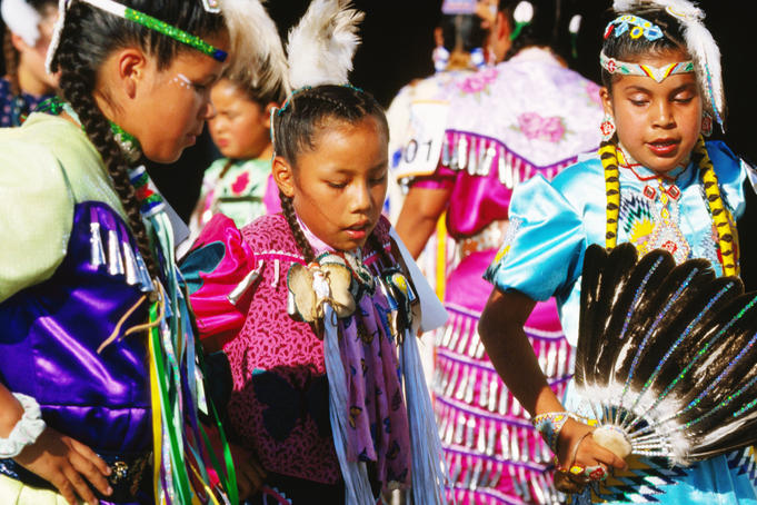 Native AMerican Indian girls in traditional dresses practice dance outside dance competition arena at Mashantucket Pequot Tribal Nation hosted Schemitzun Powwow.