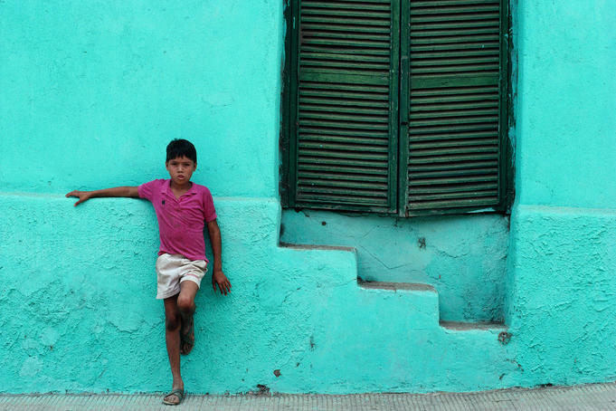 Boy standing against a wall.