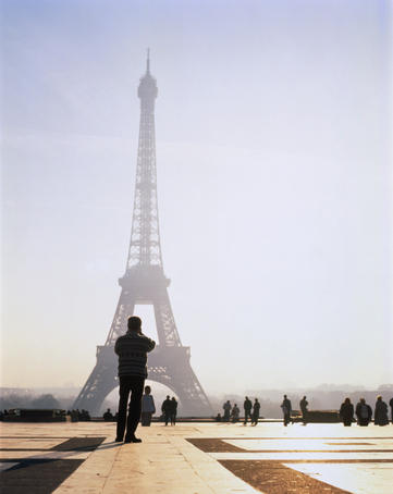 Tourist taking photograph of the Eiffel Tower.