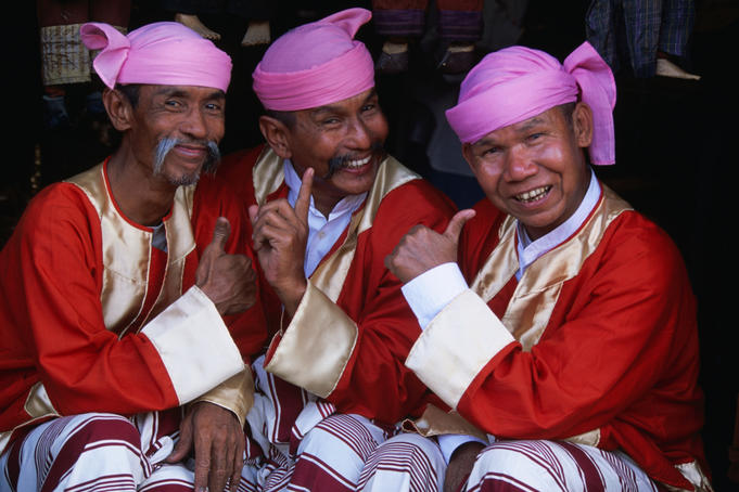 Three men in traditional clothing and headwear, known as the Moustache Brothers, giving the thumbs up