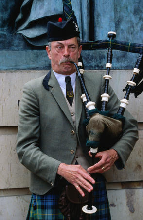 Piper playing bagpipes in Royal Mile.