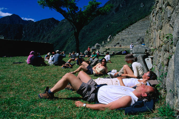 Tourists rest on the grounds of the 500 year old Inca city of Machu Picchu, discovered in 1911 by American Hiram Bingham (with a lot of help from local farmer Melchior Artega).