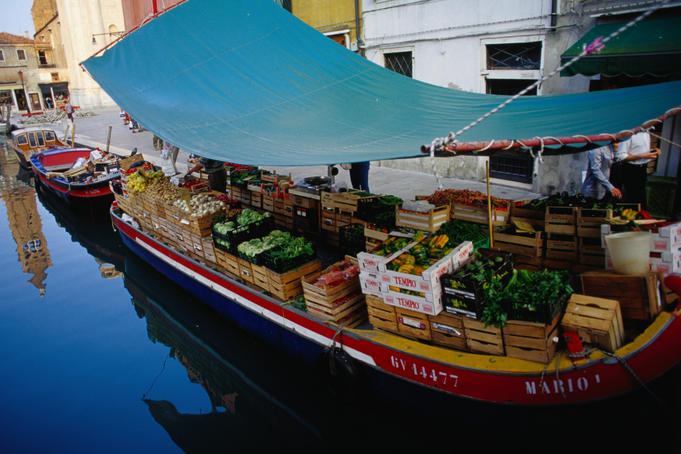 A green grocer sells wares from a 'peata', a type canal boat, on Rio di San Barnaba, Dorsodura.