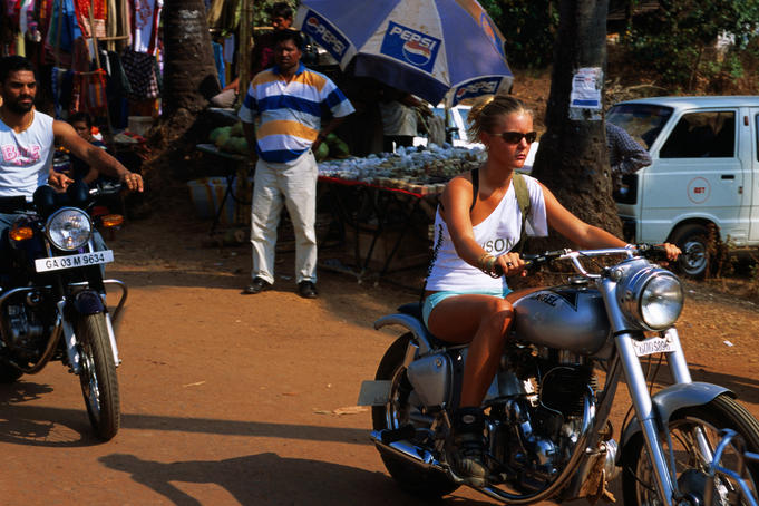 Tourist and local arriving at Anjuna Flea Market on motorbikes.