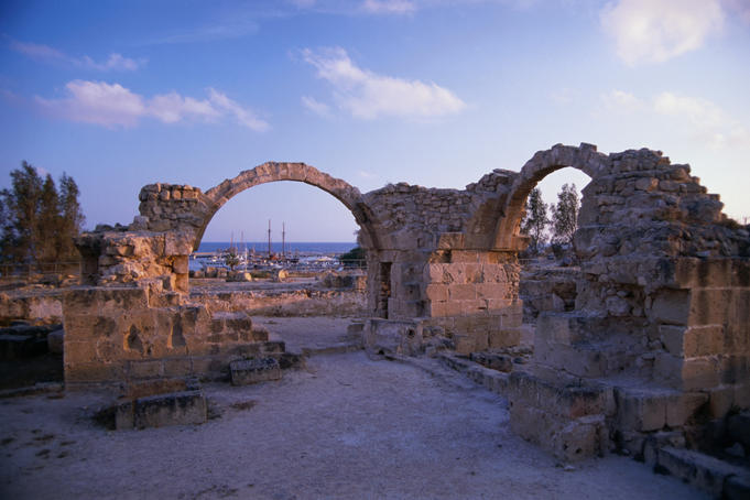 Saranda Kolones ruins at dusk in Kato Phaphos with the harbour in the background.