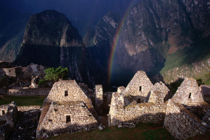 Rainbow over the remaining stone structures in the city sector of Machu Picchu.
