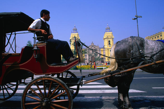 Horse and carriage waiting for customers on the Plaza de Armas with the Cathedral of Lima behind.