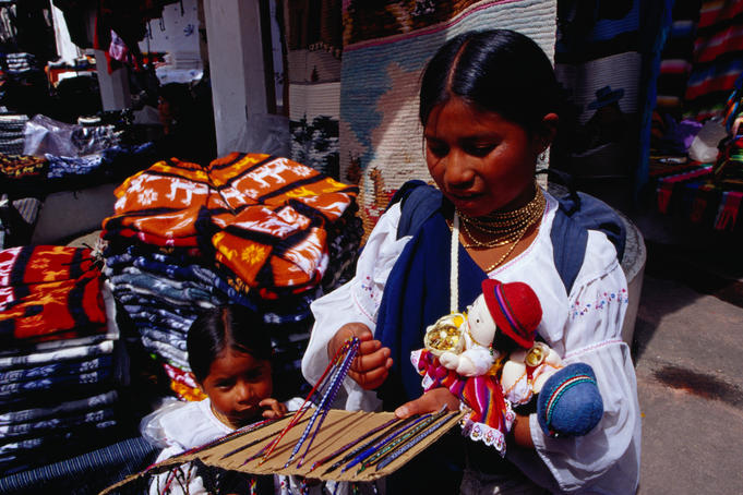 Otavaleno Indian children selling friendship bracelets and dolls at the Poncho Plaza in Otavalo.