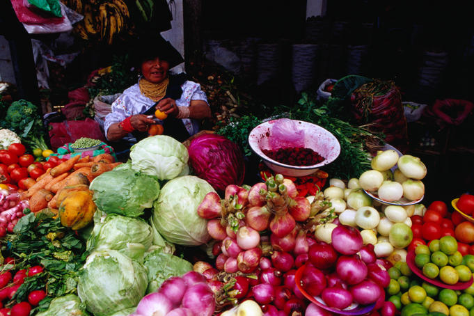 Otavaleno Indian woman and her fresh vegetable stall at the Poncho Plaza in Otavalo.