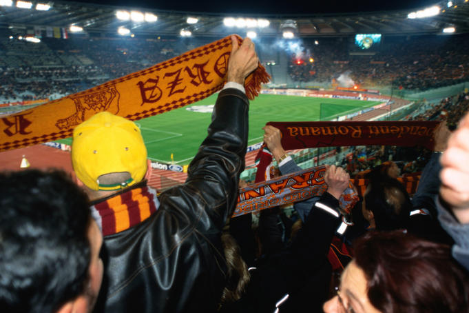 Soccer fans waving scarves at AS Roma versus Ajax Amsterdam match at Champions League Game Stadio Olimpico.