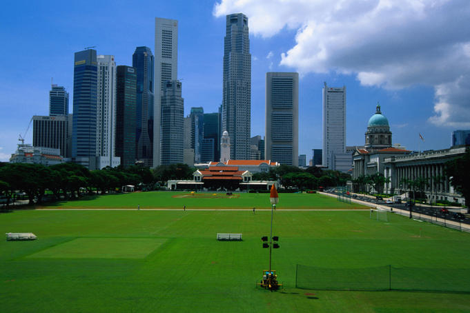 Grassy Padang and city skyline.